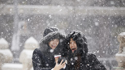 Women smile as they look at a picture on a mobile phone during snowfall in winter in central Seoul, South Korea.