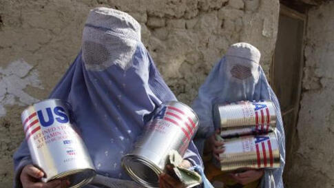 Afghan widows carry out cans of cooking oil from the United Nations World Food Program bakery in Kabul, Afghanistan, Wednesday, Nov. 21, 2001. About 350 widows, identified as the most vulnerable group in the city, received two cans of oil and two sacks of