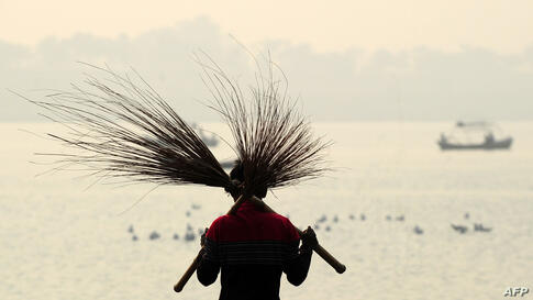 An Indian laborer carries a pair of brooms while cleaning at the Sangam, the confluence of the three rivers Ganges, Yamuna and mythical Saraswati, ahead of the annual Magh Mela festival in Allahabad.