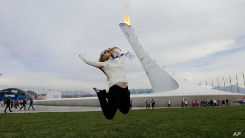 Evgenii Itbaev leaps as a friend takes her picture near the Olympic Cauldron at the 2014 Winter Olympics, Feb. 14, 2014.