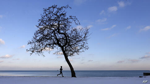 A lone runner traverses the bike and running path along Lake Michigan at the North Avenue beach as temperatures hover around freezing in Chicago, Dec. 17, 2013.