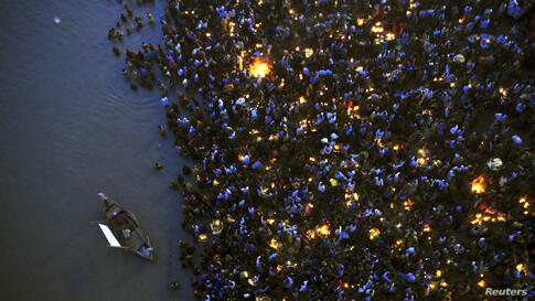 Hindu devotees gather to worship the Sun god Surya on the banks of the Ganges River during the Hindu religious festival of Chatt Puja in the eastern Indian city of Patna, Nov. 9, 2013.