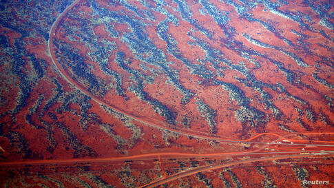Roads go off in various directions next to sand dunes covered in vegetation in the Pilbara region of Western Australia.