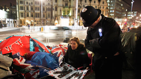 A policeman chats with a woman who spent the night opposite Westminster Abbey.(REUTERS/Nir Elias)