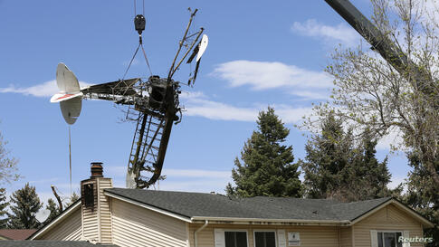 The wreckage of a small plane that crashed into a house is lifted by a crane in Northglenn, Colorado, USA, May 6, 2014. The pilot of a single-engine airplane pulling an advertising banner walked away uninjured after it crashed into an unoccupied home i...