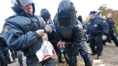 Riot police detain an anti-gay protester during an authorized gay rights rally in St. Petersburg, Russia. A gay rights rally has ended in scuffles after several dozen protesters were confronted by about 200 conservative and religious activists.
