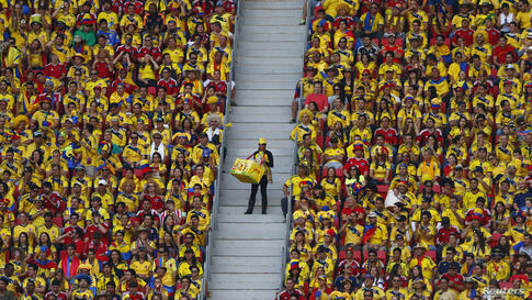 A vendor walks down the stairs as fans watch the 2014 World Cup Group C soccer match between Ivory Coast and Colombia at the Brasilia national stadium in Brazil.
