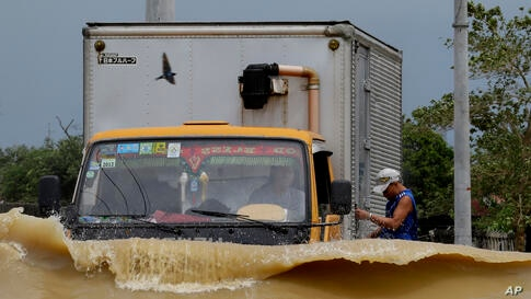 A truck driver braves the raging floodwaters brought about by Typhoon Nari along a highway at San Ildefonso township, Bulacan province, north of Manila, Philippines. At least 13 people have been killed after the storm battered across the northern Phili...