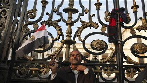 An anti-government protester gestures as he sits outside the Egyptian Parliament in Cairo, Egypt, Wednesday, Feb. 9, 2011. Around 2,000 protesters waved huge flags outside the parliament, several blocks from Tahrir Square, where they moved a day earlier i
