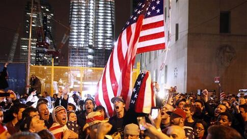 With the new One World Trade Center building in the background, second left, a large, jubilant crowd reacts to the news of Osama bin Laden's death at the corner of Church and Vesey Streets, adjacent to ground zero, during the early morning hours of Tuesda