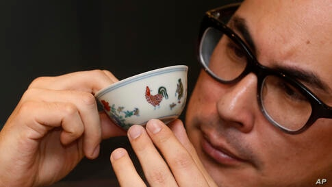 A staff member from Sotheby's presents the Meiyintang 'Chicken Cup' from the Chinese Ming Dynasty (1368-1644) during the media preview for the auction of Fine Art Chinese Ceramics and Works of Art sales in Hong Kong.