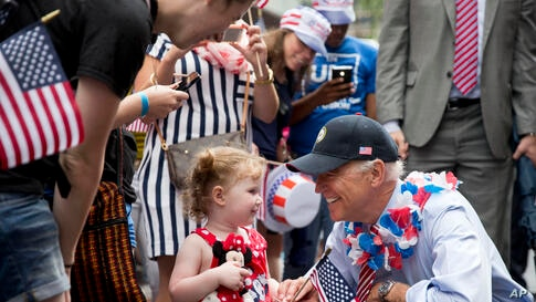 U.S. Vice President Joe Biden greets a young spectator as he marches in an Independence Day parade at Independence Hall in Philadelphia, Pennsylvania.