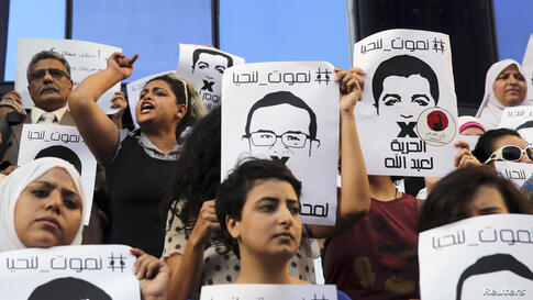 Protesters rally in front of the Press Syndicate in Cairo in support of Al Jazeera journalists Abdullah al-Shami and Mohamed Bader, who were detained by Egyptian authorities.
