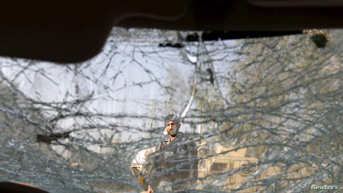 An Afghan man is seen through the cracked window of a vehicle at the site of a suicide car bomb attack in Surkhrod district of Nangarhar province.