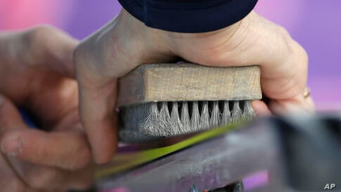 A waxing technician brushes a ski during the cross-country sprint competitions,Krasnaya Polyana, Feb. 11, 2014.