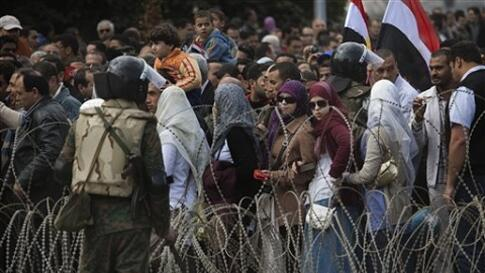 Egyptian anti-Mubarak protesters are seen behind barbed wire as they arrive at Tahrir square in downtown Cairo for more protests, Sunday, Feb. 6, 2011