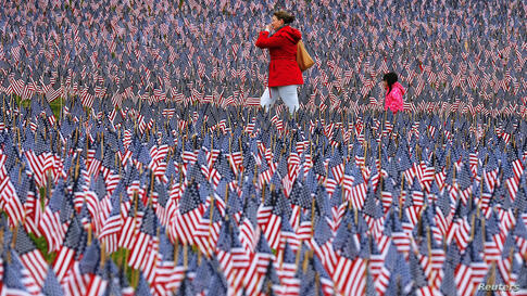 Pedestrians walk through of the field of United States flags displayed by the Massachusetts Military Heroes Fund on the Boston Common in Boston, Massachusetts ahead of the Memorial Day holiday. The 37,000 U.S. flags are planted in memory of every falle...