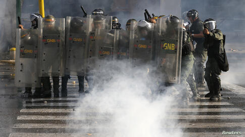 National Guards advance on anti-government protesters during clashes with police at Altamira square in Caracas. Opponents of Venezuela's socialist government marched to protest against alleged Cuban interference in the armed forces, with clashes breaki...