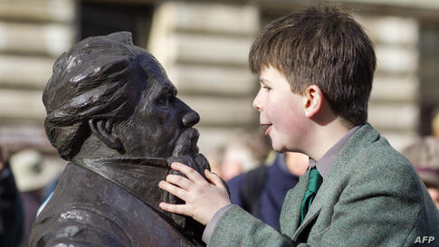 Oliver Dickens, 9, looks at the newly installed statue of his late great, great, great grandfather British writer Charles Dickens at Guildhall Square in Portsmouth.