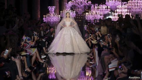 A model presents a wedding dress creation by Lebanese designer Elie Saab as part of his Haute Couture Fall/Winter 2014-2015 fashion show in Paris, France.