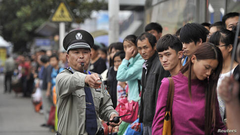 A security guard gestures as he blows a whistle at a bus stop outside the city's railway station, during a traffic peak on the last day of China's National Day Golden Week in Hefei, Anhui province.