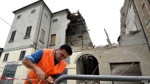 A volunteer ropes off the area surrounding a collapsed building in Finale Emilia, northern Italy after a quake hit northern Italy May 20, 2012. (AP Photo/Marco Vasini)