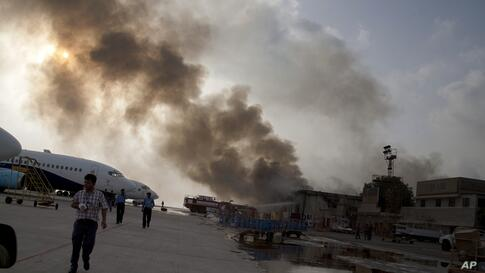 Smoke rises above the Jinnah International Airport where security forces continue to battle militants in Karachi, Pakistan, June 8, 2014. Gunmen disguised as police guards attacked a terminal with machine guns and a rocket launcher during a five-hour s...
