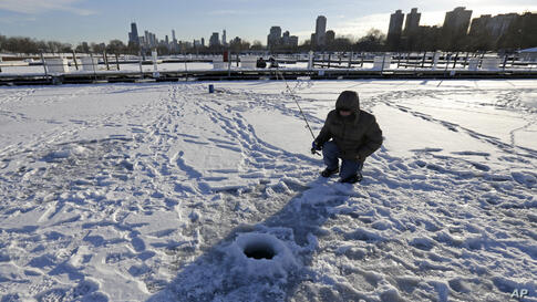 A man ice fishes at Lake Michigan Water Trail Launch Site in Chicago, Illinois, Dec. 18, 2013.