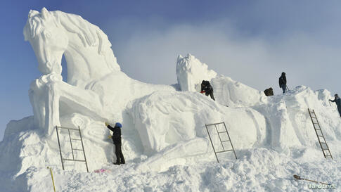 Workers shape a giant snow sculpture of horses, ahead of an ice and snow festival in Barkol Kazakh Autonomous County, China's far western region of Xinjiang.