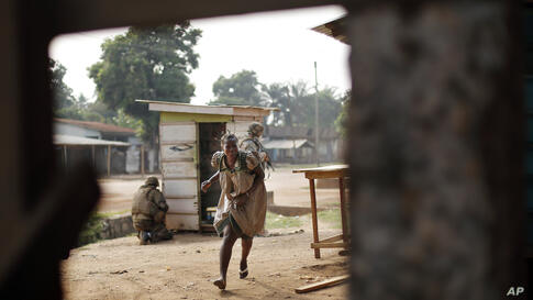 A woman runs for cover as heavy gunfire erupts in the Miskin district of Bangui, Central African Republic. In what a French soldier on the scene described as the heaviest exchange of fire he'd seen since early December 2013, Muslim militias engaged Bur...