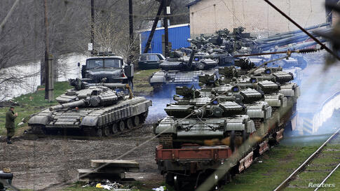 A Russian soldier (L) guides a Ukranian tank which will be loaded onto a train in northern Crimea.
