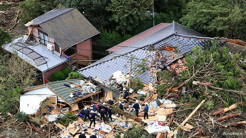 An aerial view shows rescue workers searching among collapsed houses following a landslide caused by Typhoon Wipha on Izu Oshima island, south of Tokyo, in this photo taken by Kyodo.