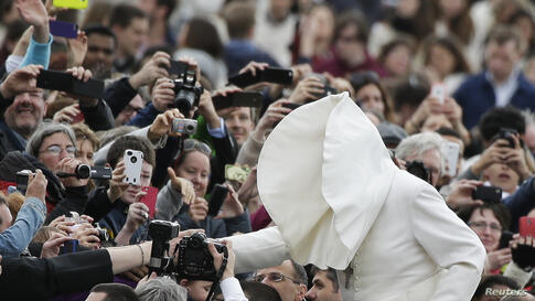 A gust of wind blows Pope Francis's mantle as he arrives to lead his Wednesday general audience in Saint Peter's square at the Vatican.