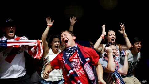 Harrison Heiman, center, and Lindsay Heiman, right, react with fellow fans while watching the 2014 World Cup soccer match between the United States and Belgium at a viewing party in Atlanta, Georgia, USA, July 1, 2014.