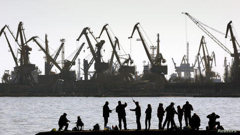 People fish on a pier at the port of Mariupol, located on the north of the Sea of Azov in eastern Ukraine.