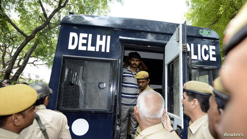 Akshay Thakur (top), one of the four men who were sentenced to death for the rape and murder of a young woman on a bus last December, disembarks a police vehicle outside a court in New Delhi.