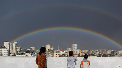 Palestinian children look at a rainbow shining over buildings after heavy rain poured in Gaza City, Gaza.