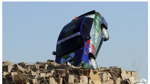 A combination picture shows a car, driven by stunt driver Xie Yujun, hitting carton boxes upon landing after it leaped over a section of the frozen Songhua River in Heihe, Heilongjiang province, near the border of China and Russia.Xie successfully lea...