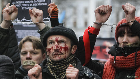 Pro-European integration supporters with taped mouths attend a rally against newly approved laws in Kiev, Ukraine. Supporters of Ukrainian President Yanukovich rammed a sweeping law through parliament on Thursday in an attempt to curb anti-government p...