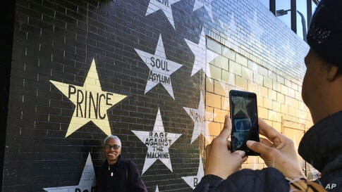 Fans take photos outside First Avenue nightclub in Minneapolis, Minnesota. People stopped by the star-painted wall Friday to remember and pay respects to Prince on the one-year anniversary of his death from an accidental fentanyl overdose.