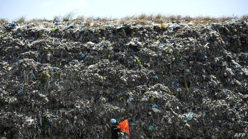 A man carrying his son walks in front of a landfill near Manila Bay, Philippines.