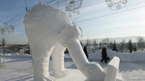 "Pedestrians walk past the ""Computeriada"" snow sculpture created by the ""Latvia Team"" from Pavilosta, during  ""The Magical Ice of the Siberia"" festival on the bank of the Yenisei River in Krasnoyarsk, Russia. More than 20 teams of ice and snow sculptors..."