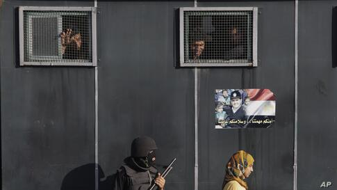 An Egyptian woman walks past a vehicle carrying anti-riot police officers deployed to secure a protest against sexual harassment in Cairo, June 14, 2014.