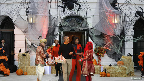 U.S. President Barack Obama (center left) and first lady Michelle Obama (center right) give Halloween treats to visiting children at the White House in Washington, D.C., Oct. 31, 2013.