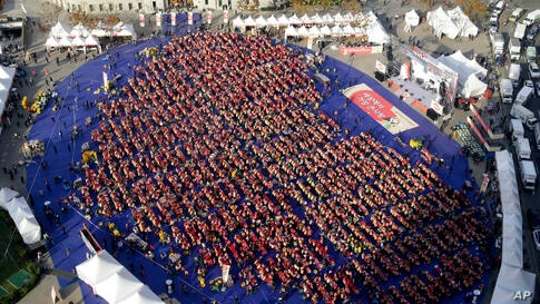 Participants arrange themselves in the shape of a heart while making kimchi, a traditional South Korean pungent vegetable dish, in front of Seoul's City Hall in South Korea, to donate to needy neighbors in preparation for the winter season as they atte...