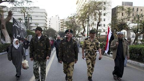 An Egyptian Major-General, center, walks with his officers outside the Egyptian Parliament in Cairo, Egypt, Wednesday, Feb. 9, 2011. Around 2,000 protesters waved huge flags outside the parliament, several blocks from Tahrir Square, where they moved a day