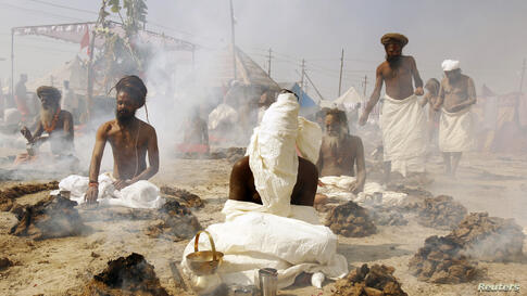 """Sadhus, or Hindu holy men, perform prayers while sitting inside circles of burning """"Upale"""" (or dried cow dung cakes) on the banks of the Ganges River during the Magh Mela festival in the northern Indian city of Allahabad."""