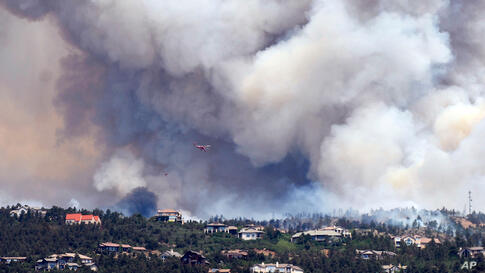 Smoke billows from a wildfire burning near Colorado Springs, Colo., on Sunday, June 24, 2012. The fire erupted and grew out of control to more than 3 square miles early Sunday, prompting the evacuation of more than 11,000 residents.
