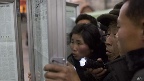 A North Korean man uses a flashlight as he and other subway commuters gather around a public newspaper stand on a train platform in Pyongyang to read headlines about Jang Song Thaek, North Korean leader Kim Jong Un's uncle, who was executed as a traito...