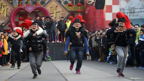 Men wearing pig masks carry their girlfriends on their backs as they run to be selected as finalists during a kissing contest held in celebration of Valentine's Day at the Happy Valley amusement park in Beijing, China. About 100 couples competed in the...